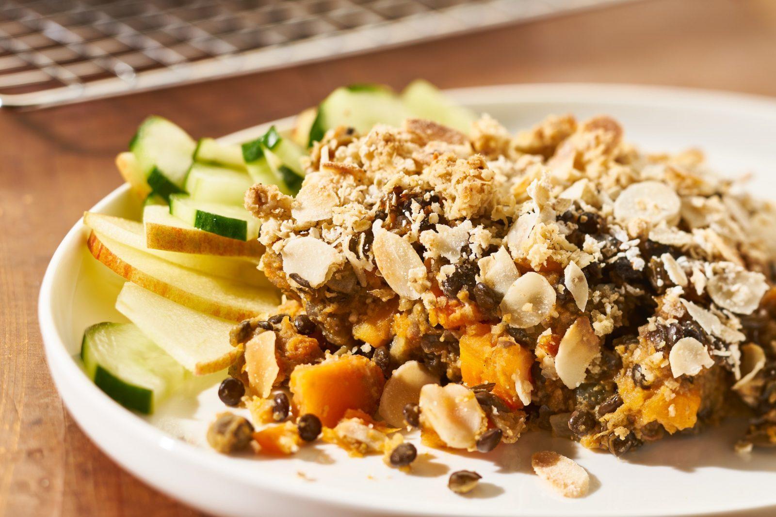 Zoete aardappel linzen ovenschotel met notencrumble en frisse komkommer appelsalade